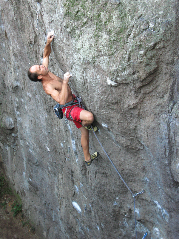 Leonardo di Marino crimping hard on the crux hold of his route Fixiren 8a, Punta della Croce, Planetmountain