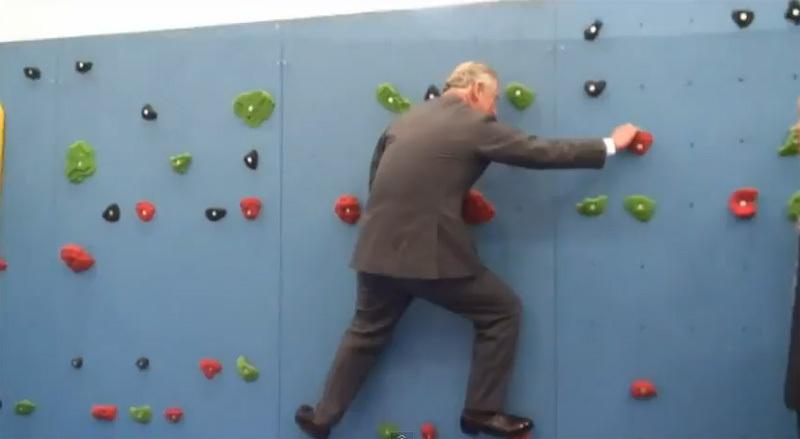 Il Principe Carlo attraversa un muro d'arrampicata sull'isola di Jersey, UK,