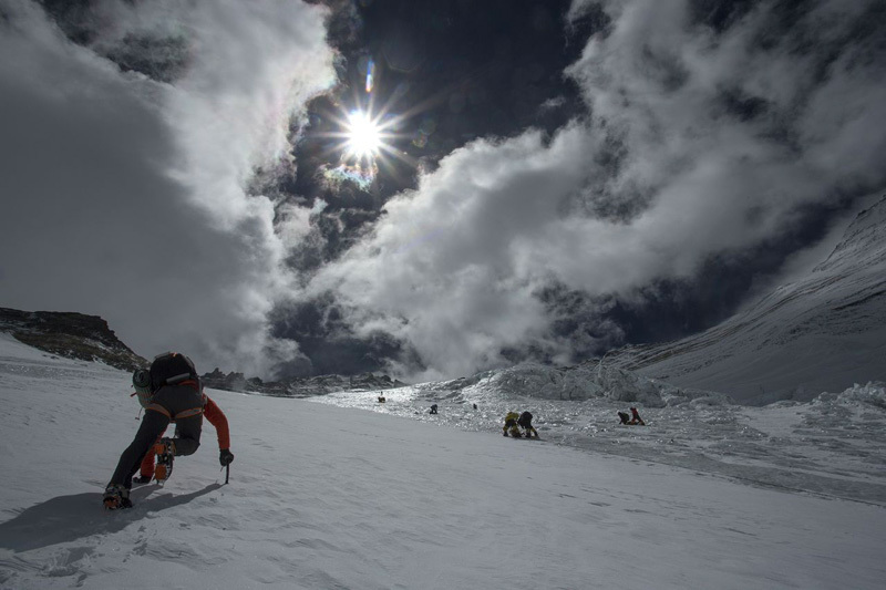 Ueli Steck ascending the Lhotse Face, with Sherpas on the right., Jon Griffith