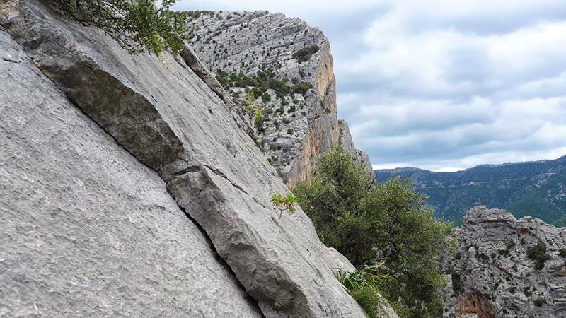 Los Compadres (325m, 5c+, Corrado Pibiri, Vincenzo Carcangiu 2013): Di fianco, la parete Sud di punta S'Iscopargiu. Sulla sfondo la SS125, archivio Vincenzo Carcangiu