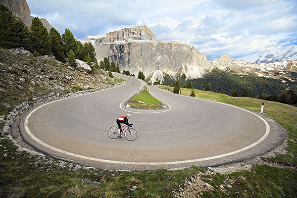 Amy Rasic riding through the steep, hairpin turns of the Sella Pass above Canazei, Italy, PatitucciPhoto