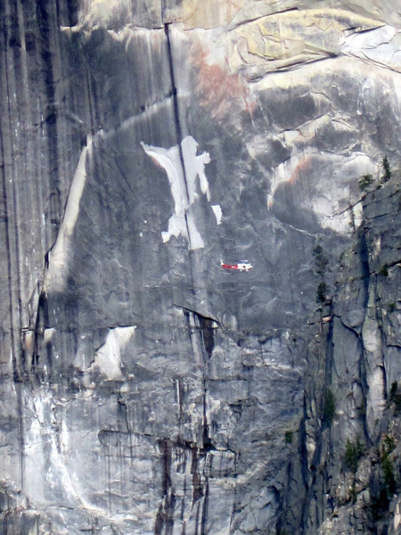 Helicopter surveying the aftermath of the rockfall on Half Dome in Yosemite. The scar behind the helicopter is the result of a previous rockfall., Bryce Bresline