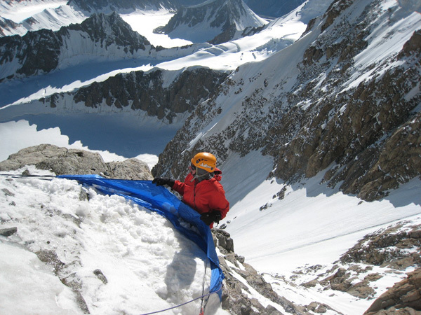 Filling the Ice Hammock with snow to build up a bivy ledge, Steve Swenson