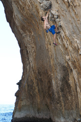 Mike Rolf during the first ascent of Tramonti 7a, a Deep Water Solo route up the Lover's Arch, Faraglioni, Capri.
