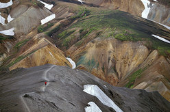 Runner dwarfed by the large, colorful landscape on an uphill slog in Blahnukur-Landmannalaugar, Iceland.