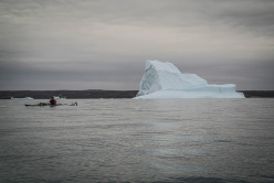 Silvan Schüpbach kayaking past the icebergs.
