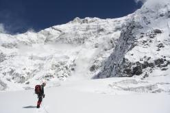 Alberto Peruffo in prossimità del primo raggiungimento del futuro Colle Sella, sul punto di attacco dello Sperone Zemu alla Parete Sud del Kanchenzonga, visibile con una valanga sulla sinistra.