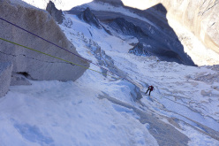 Paulo Roxo abseiling the route. The yellow bivouac tent is visible on the edge of the spur.