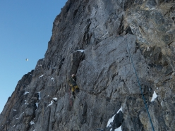 Eiger Metanoia: Thomas Huber on one of the harder pitches of Metanoia. In the sky a hot air ballon flies by.