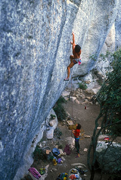 Laurence Jacob, belayed by Luisa Iovane, climbing Le nuit de lézard 8a+ at the Face Ouest at Buoux in 1986.
