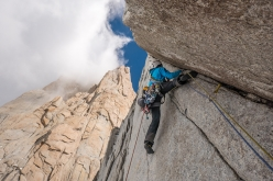 Aguja Val Biois, Patagonia: pitch 9 of La Torcida, the crux pitch. Hard from the start, with strenuous moves up the thin finger crack. In the back looms the Pilar Goretta of Fitz Roy.