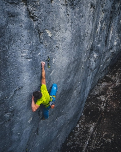 Adam Ondra on the crux move of the 9b slab Disbelief at Acephale in Canada.