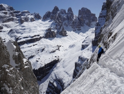Luca Dallavalle skiing down the NE Face of Crozzon di Val d'Agola in the Brenta Dolomites. From left: Cima Brenta, Spallone Massodi, Torre di Brenta, Sfulmini, Campanil Alto, Campanil Basso, Cima Brenta Alta