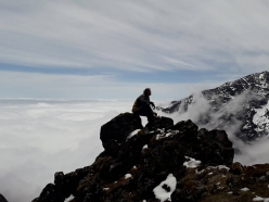 Tomas Franchini above a sea of clouds observing the East Face of Lamo She in China, climbed solo by