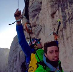 Aaron Durogati and Mirco Grasso flying past the South Face of Marmolada in the Dolomites after having taken off from the ledge at half-height