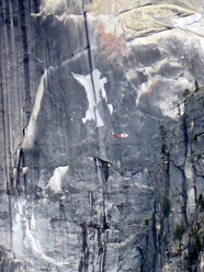 Helicopter surveying the aftermath of the rockfall on Half Dome in Yosemite. The scar behind the helicopter is the result of a previous rockfall.