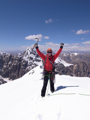 Kristoffer Szilas on the summit of Peak Alexandra with the still unclimbed Pt 5318 in the background.